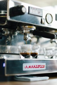 Espresso machine with two espressos brewing.  Photo by David Lundgren on Unsplash