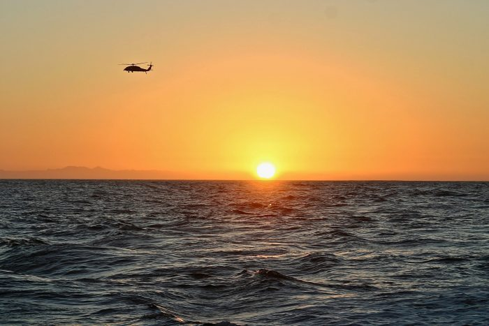 helicopter over ocean at sunset